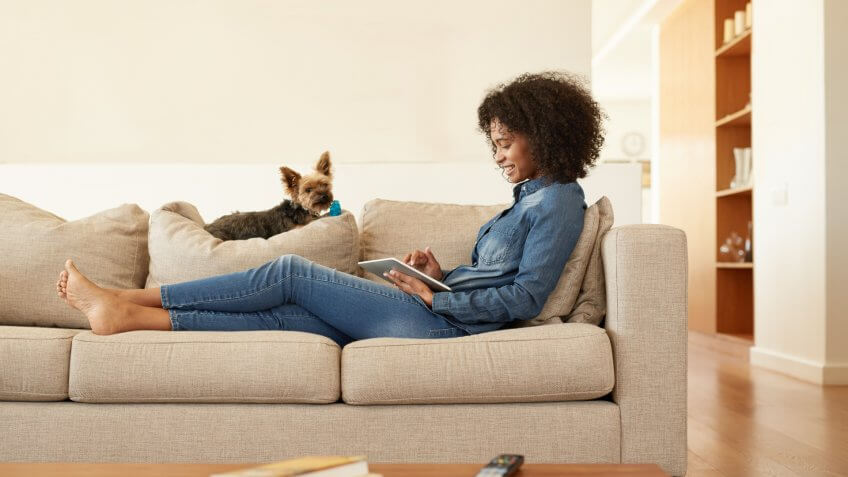 Shot of a young woman relaxing on the sofa with her digital tablet at home.