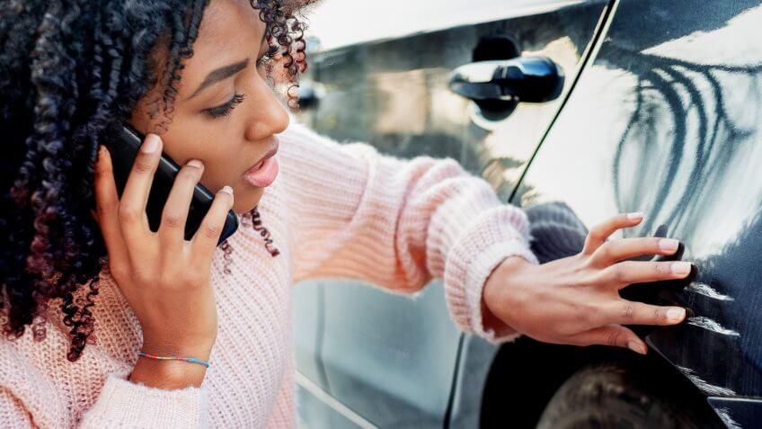 Black woman feeling sad after scratching car bodywork.