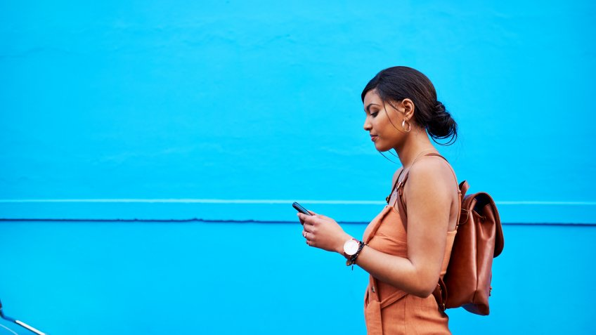Shot of an attractive young woman using a cellphone while traveling with her bicycle against a blue background outdoors.