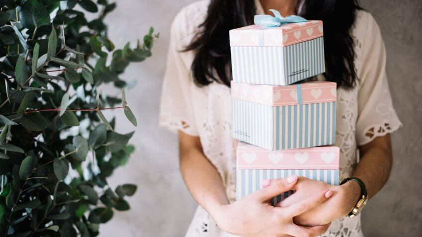 Very nice young woman holding piled colourful gift boxes with eucalyptus on the background.