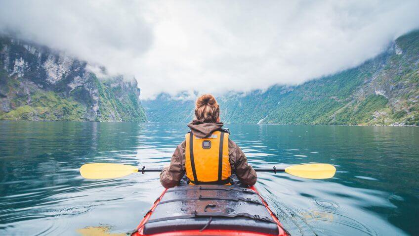 Woman kayaking in Geiranger fjord in Norway.