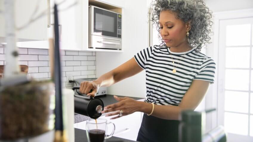 A beautiful black woman with white curly hair makes coffee.