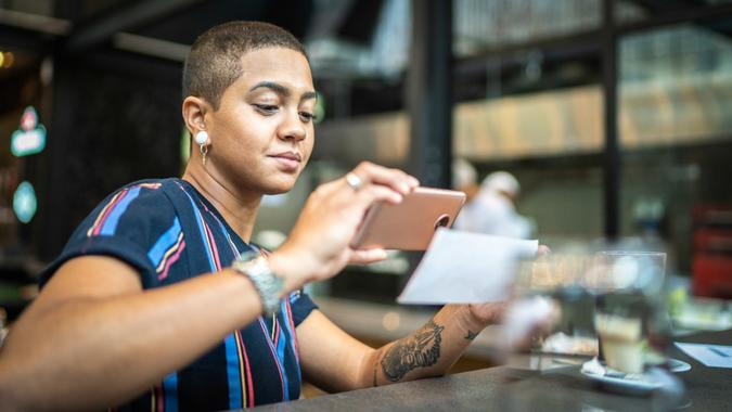 Young woman depositing check by phone in the cafe.