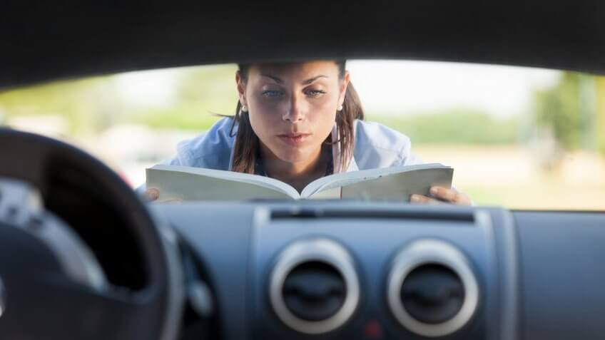 woman reading owners manual from car