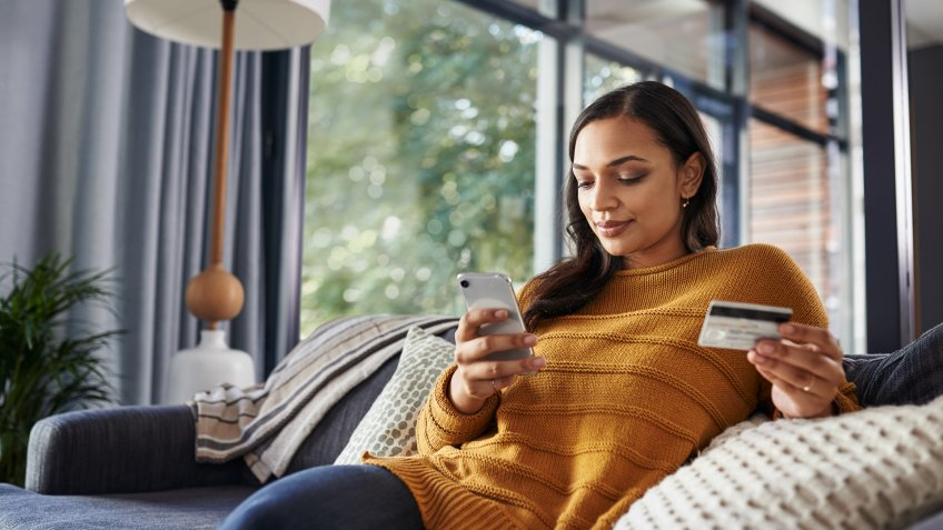 Shot of a beautiful young woman using her cellphone and credit card while relaxing on a couch at home.