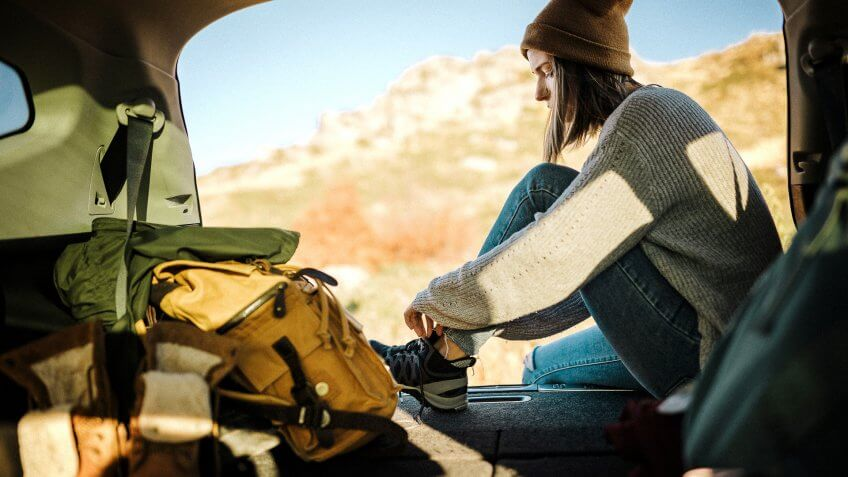 Young woman sitting in car trunk and tying her shoelaces on snickers.