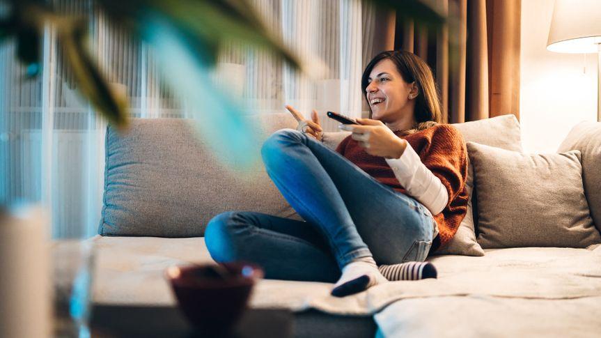 Young woman watching TV at night, at the apartment, Hamburg, Germany.