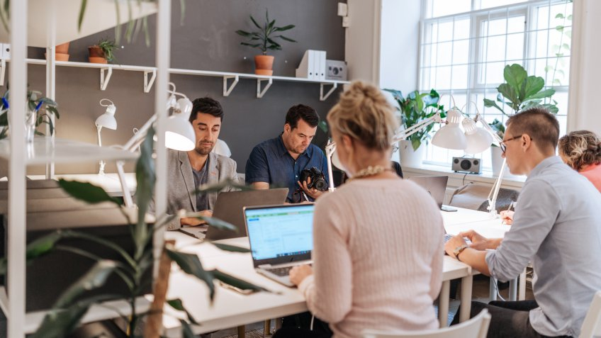 Coworkers working in modern co-working space in Scandinavia.