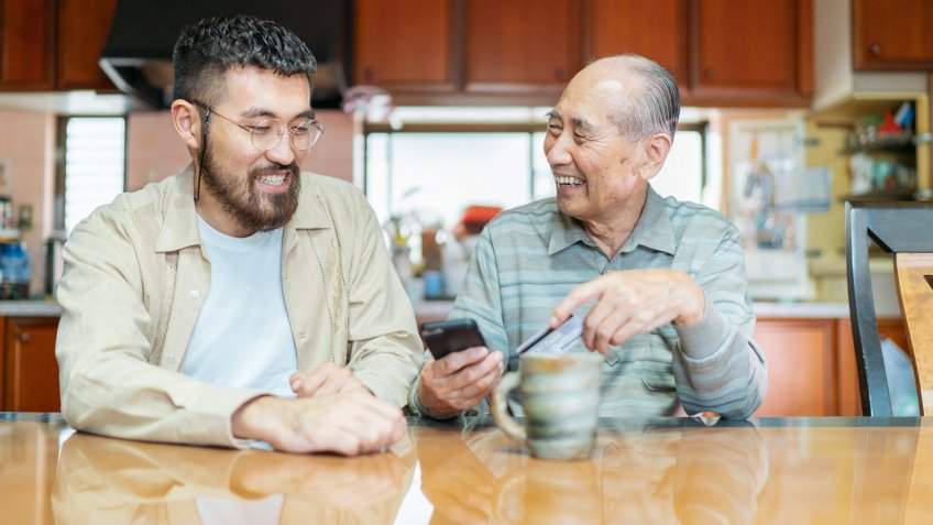 A young man is helping his grand father with shopping online and using a credit card on a smart phone.