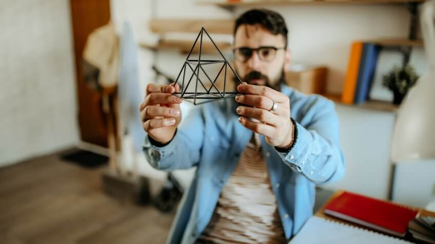 Hipster men examining pyramid for designing full product.