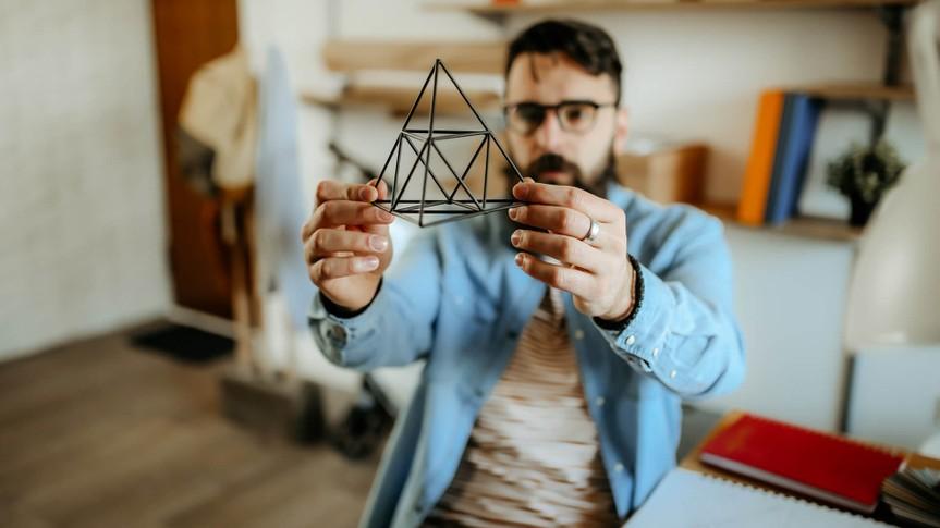 Hipster men examining pyramid for designing full product.