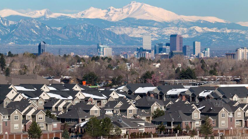 The snow covered Longs Peak and the Rocky Mountains stand behind Downtown Denver skyscrapers, hotels, office and apartment buildings with homes and condos in the foreground.