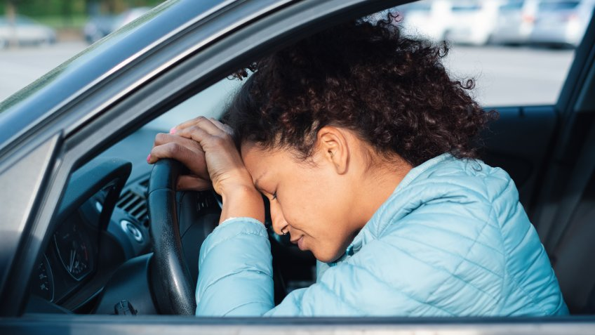Frustrated woman stuck in traffic jam.
