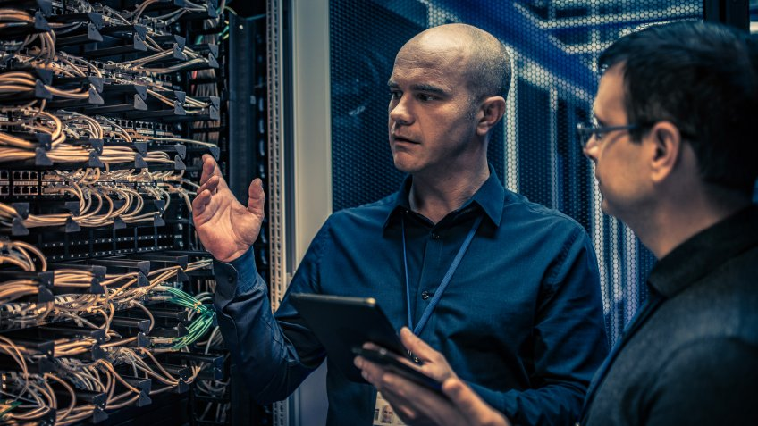 Photo of an IT engineer with a digital tablet explaining server configuration and operation to his supervisor.