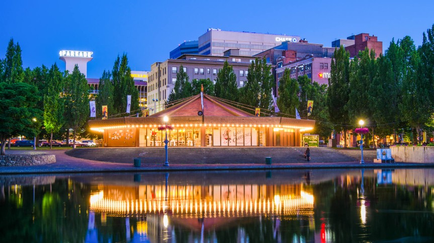 """""""Spokane, United States - July 21, 2012: People mill around outside the 1909 Looff Carousel, which is seen along the Spokane River with the downtown district of Spokane in the distance."""