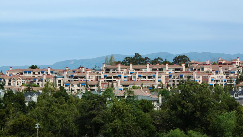 Hillside housing development sports tile roofs and blue awnings.