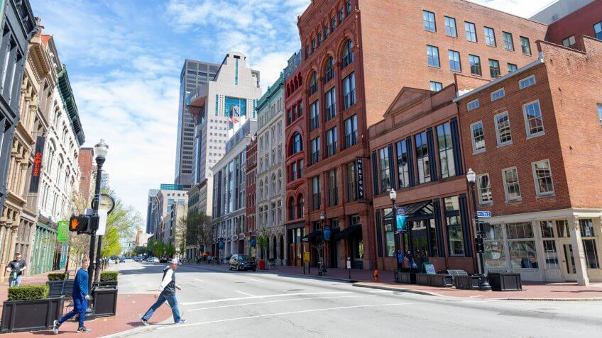 Louisville, Kentucky, USA - April 13, 2019: People walking on West Main Street, among the old buildings at downtown.