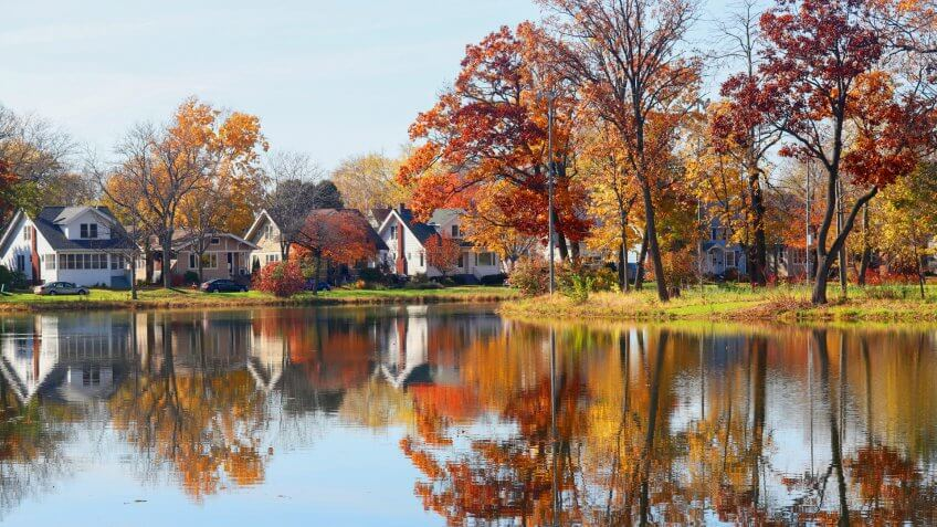 Fall view of private houses neighborhood with classic american middle class homes and colorful trees along a pond reflected in a water.