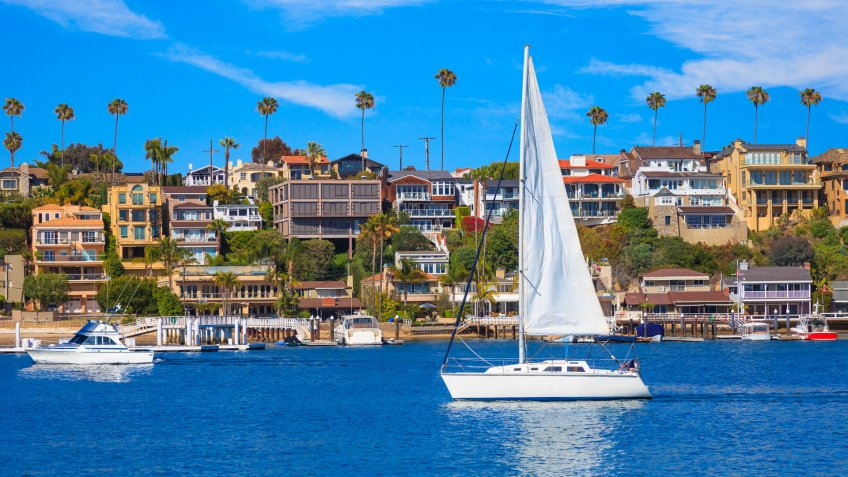 Recreational sailboat sailing on calm harbor waters of Newport Bay with beach houses and Fashion Island in background.