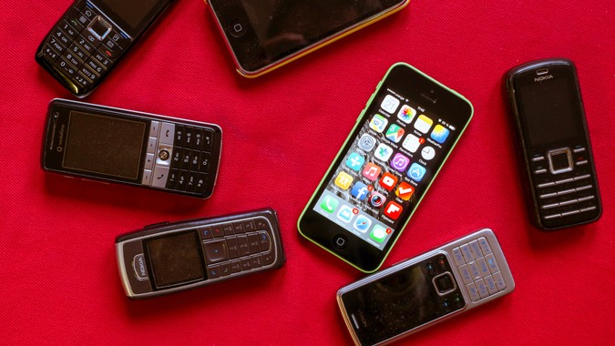 BUCHAREST, ROMANIA - MARCH 17, 2014: Photo of iphone versus old Nokia phones on a red background showing the evolution of mobile phones.