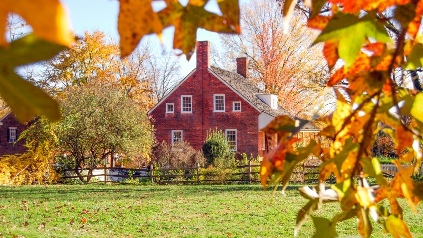 """Brown House framed by color changing leaves."