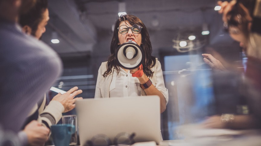 Low angle view of angry female manager yelling at her team through megaphone in the office.