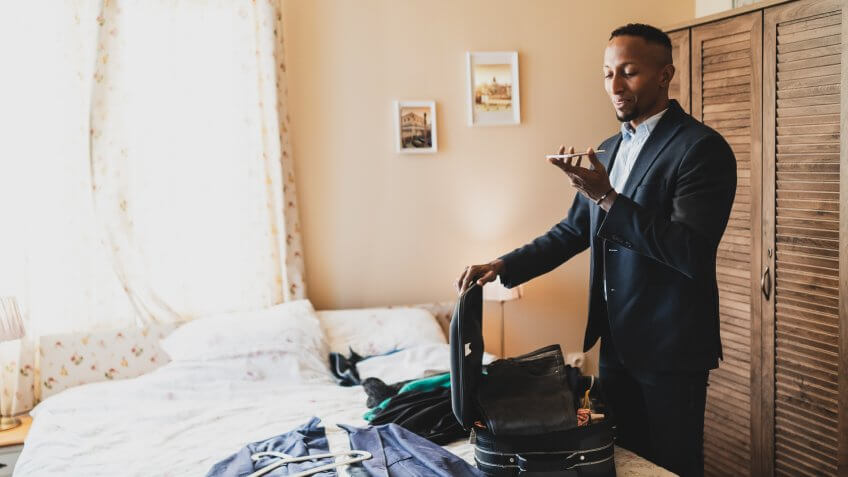 Businessman prepares his clothes in suitcase on bed.
