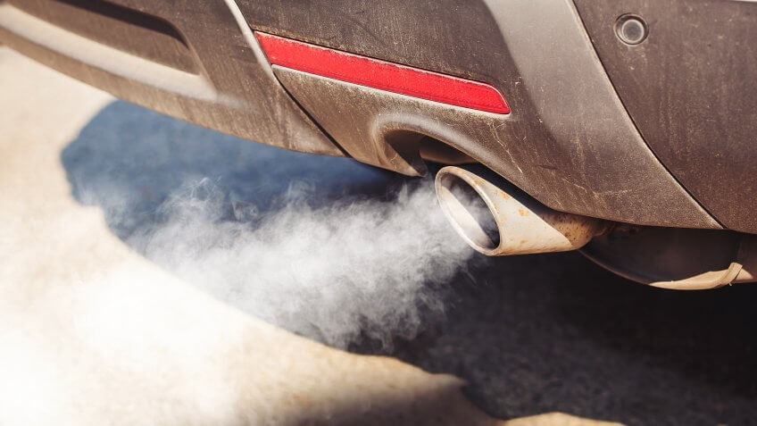 air pollution from dirty and aged vehicle exhaust pipe on road.