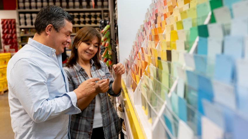Portrait of a loving couple at hardware store choosing a color to paint their house and holding a palette - decoration concepts.