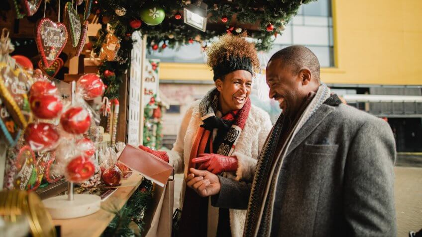 Mature couple looking at a Christmas market stall in a city centre.