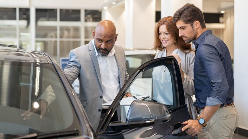 Mature african salesman showing all the car features to young couple.