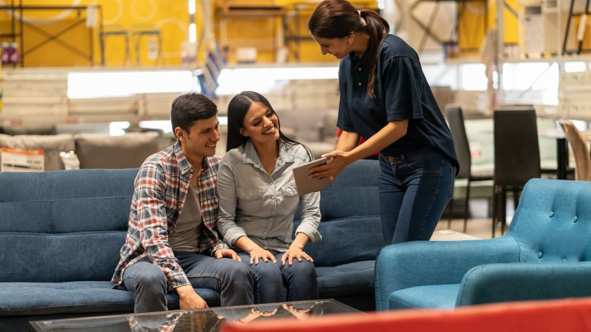 Happy saleswoman selling furniture to a couple at a home improvement store and showing them options on a tablet computer.
