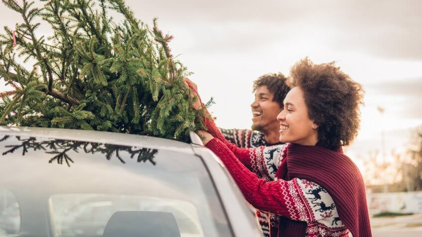 Happy young couple strapping Christmas tree to their car.