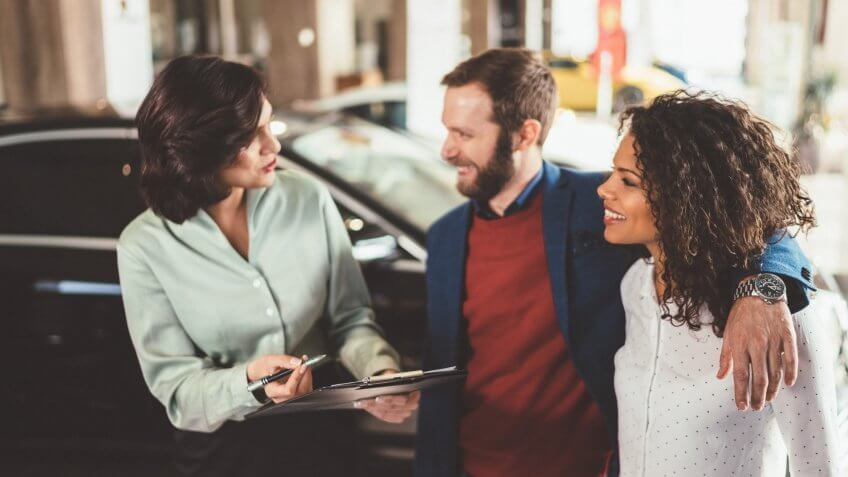 Car saleswoman assisting customers to make the best choice for buying a new car in the showroom.