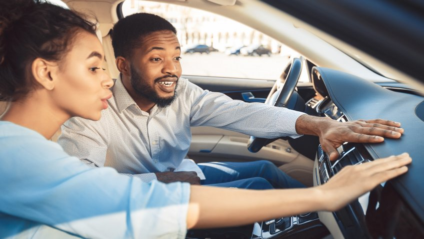 Afro couple at car showroom touching dash of new auto, sitting inside.
