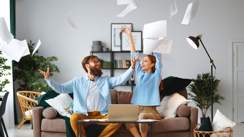 married couple with bills receipts documents and a laptop at home.