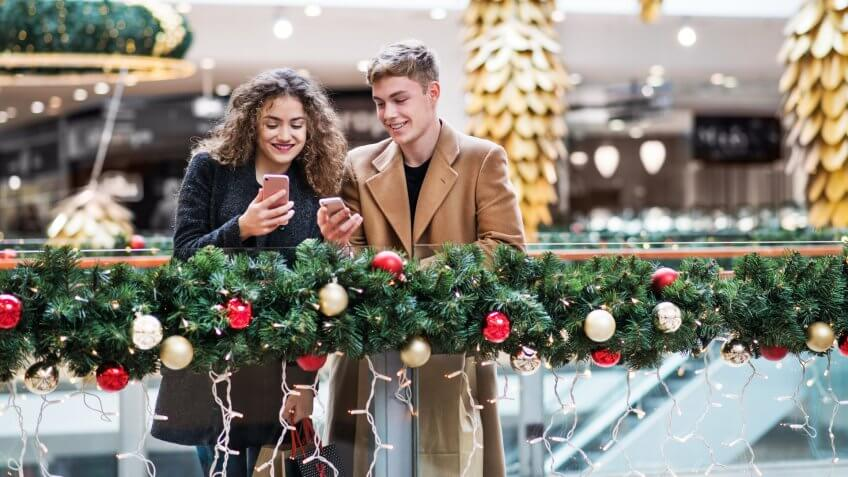 A happy young couple with smartphone in shopping center at Christmas time, text messaging.