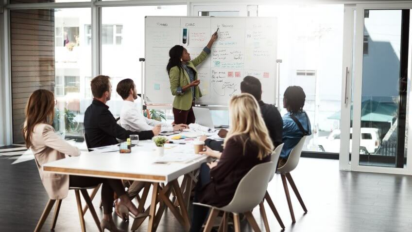 Shot of a businesswoman giving a presentation to her colleagues on a whiteboard in a boardroom.