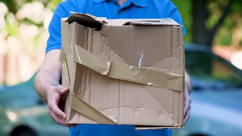 Male courier showing damaged box, cheap parcel delivery, poor shipment quality.