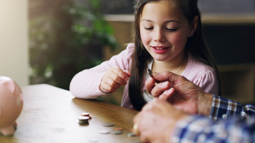 Shot of a little girl learning about money from her grandfather.