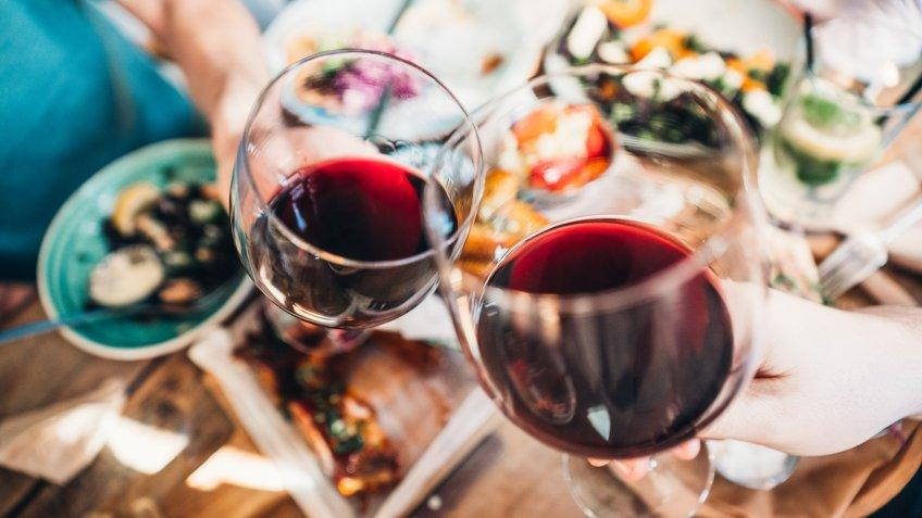 Close up of a friends toasting with red wine at restaurant.