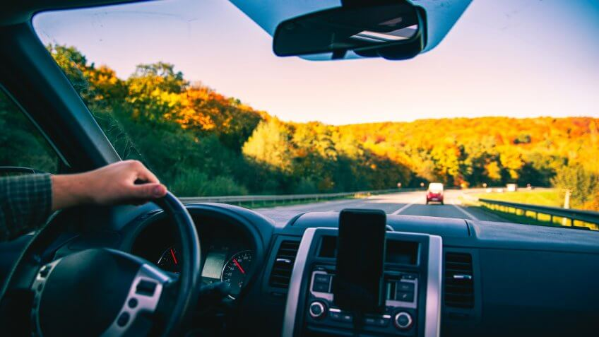 man hands on steering wheel riding by autumn speedway fall season car travel.
