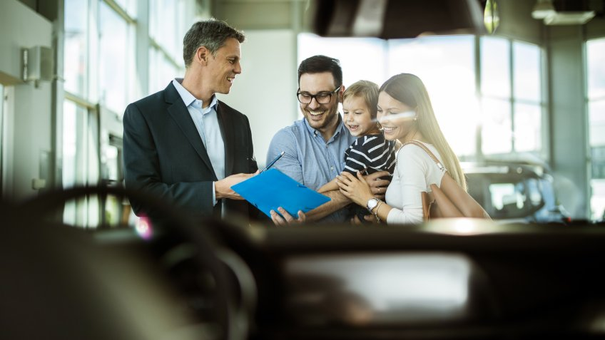 Happy family reading buying plan with salesperson in a car showroom.