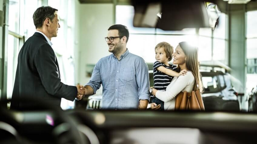 Happy family came to an agreement with salesperson in a car showroom.
