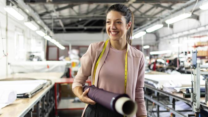 Smiling young woman working in a fashion factory.