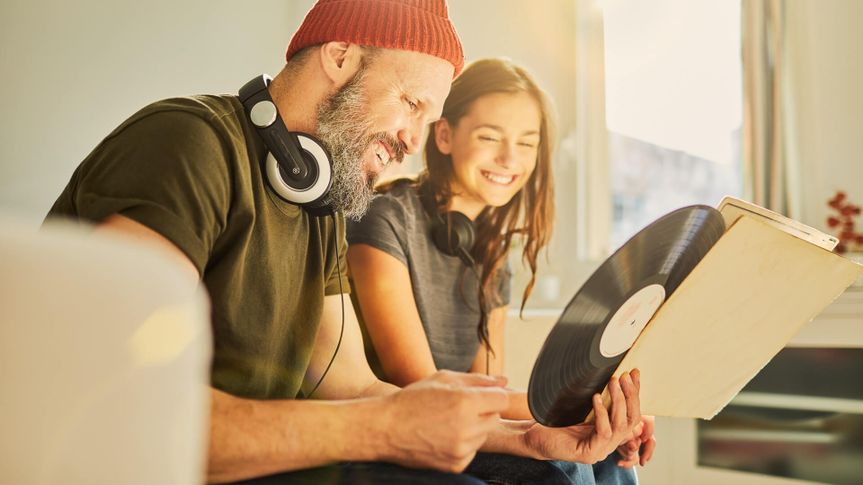 father and daughter looking at records to play on record player