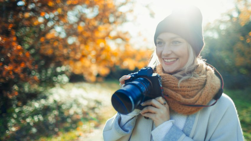 Smiling woman with digital camera in sunny autumn park.