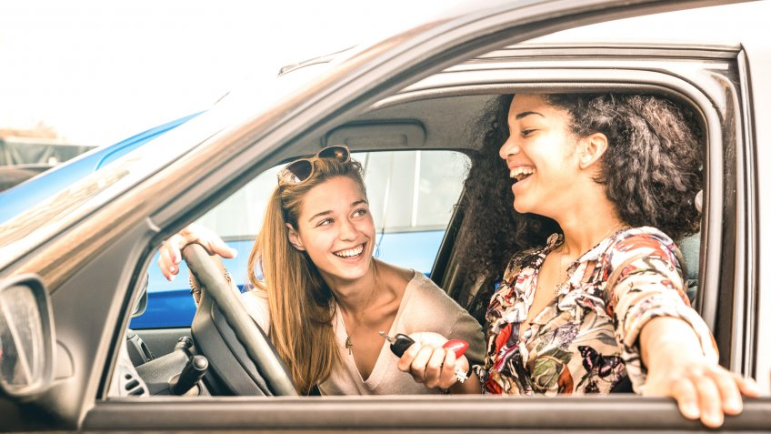 Young female best friends having fun at car roadtrip moment - Transportation concept and urban ordinary life with women girlfriends at happy travel vacation on the road - Bright azure filter.