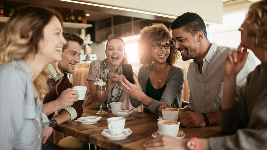 Picture of friends smiling and sitting in a cafe having coffee and using a phone.