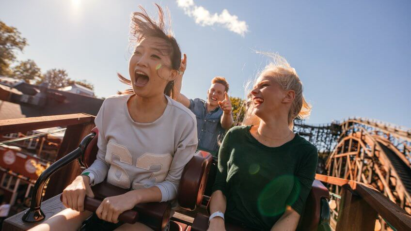 Young friends on thrilling roller coaster ride.